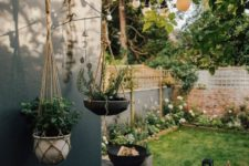 a small Nordic backyard with a black deck, a fire pit, candle lanterns, a green lawn and lots of blooms