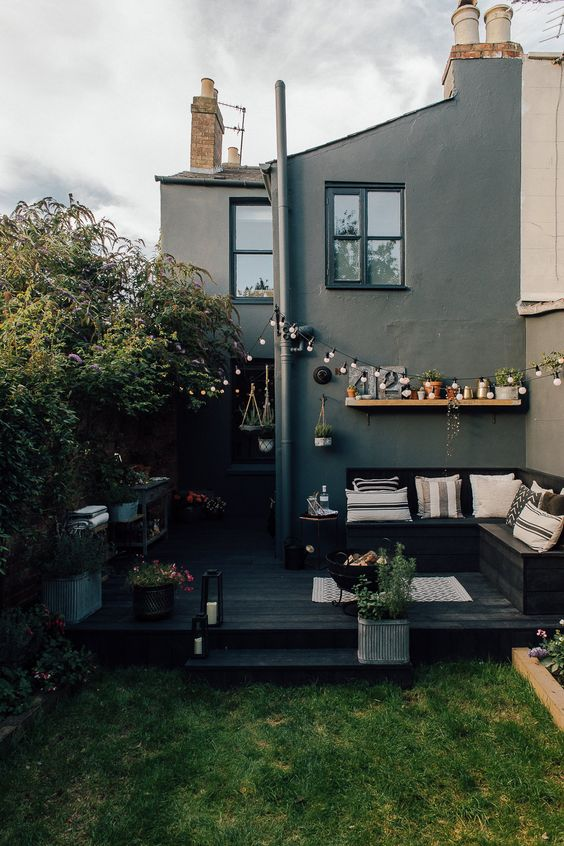 a small Scandinavian backyard with a black deck, a black corner bench, a green lawn and some blooms all around
