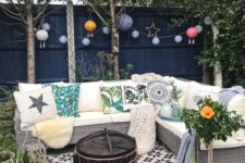 a small backyard with a green lawn, paper lamps, a wicker sofa with printed pillows and potted plants