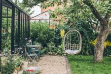 a small backyard with a suspended chair, some garden furniture, potted blooms and a green lawn