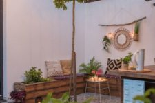 a small boho backyard with gravel on the ground, a wooden corner bench, some greenery, lights, boho pillows and lights