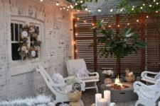 a small eclectic backyard with a fire pit, some white vintage furniture and lights all over the space