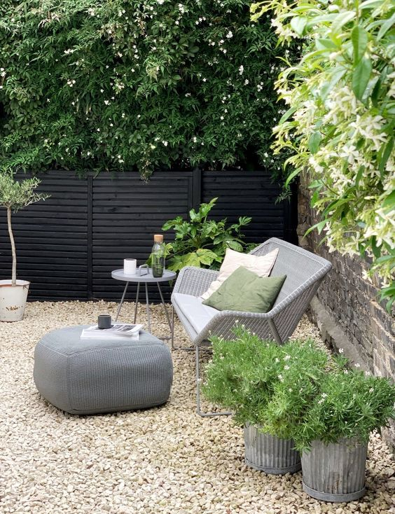 a small modern backyard with gravel on the ground, with rattan furniture and potted plants and blooms