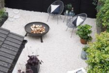 a small modern backyard with white gravel, rattan chairs, a fire pit and some potted plants is super stylish