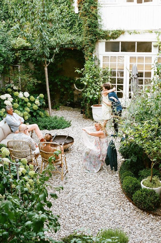 a small yet cozy backyard with gravel on the ground, some rattan furniture and lots of greenery and white blooms around