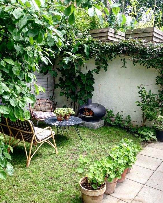a small yet cozy backyard with rattan furniture, a marble top table, a little hearth and a green lawn