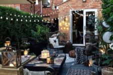 a small yet stylish backyard space with a wooden deck, lots of greenery, lights, candles and simple wooden furniture
