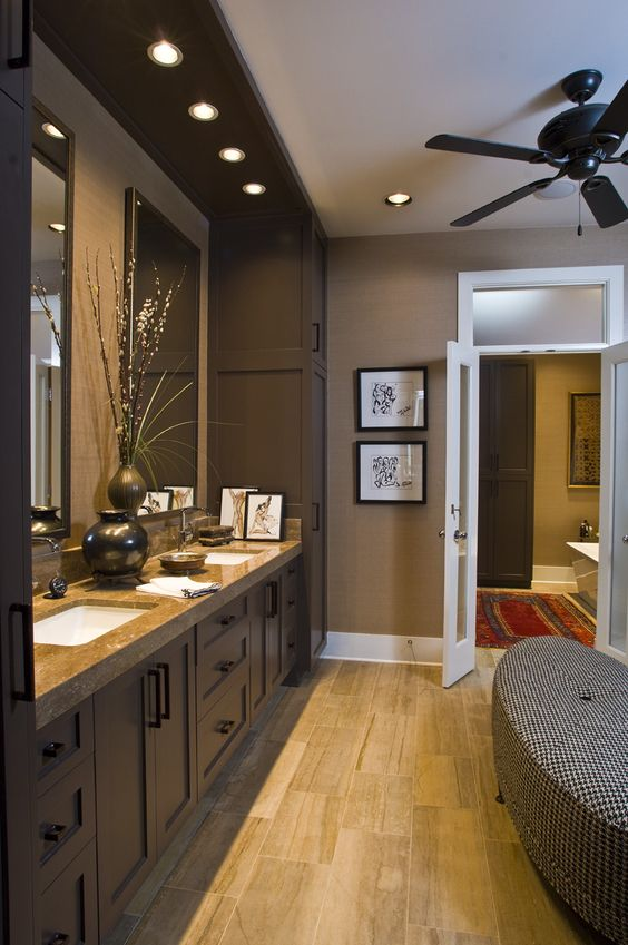 a stylish brown bathroom with tan walls, chocolate brown furniture, a stone countertop and a printed upholstered bench