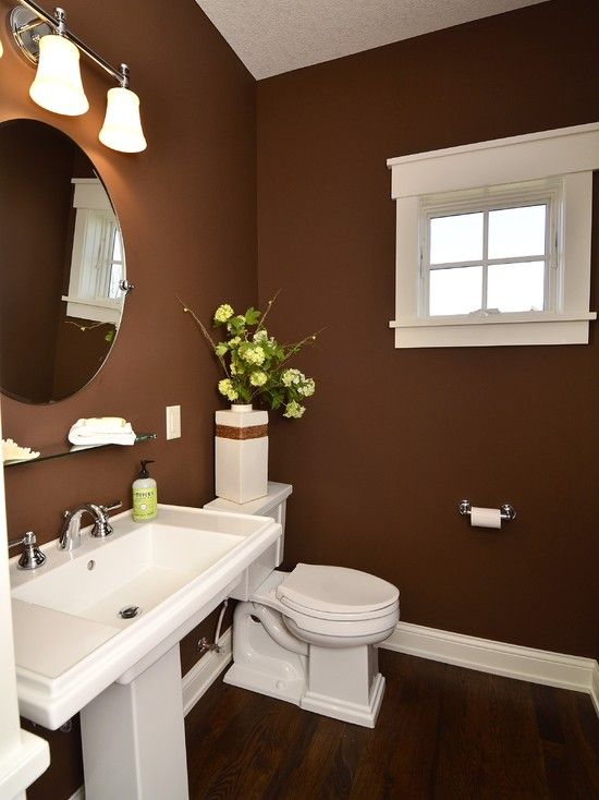 a stylish brown bathroom with white appliances and lamps and a mid-century modern feel