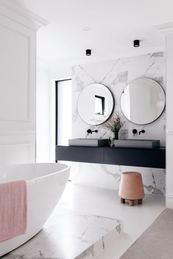 a stylish contemporary bathroom with a black floating vanity and black fixtures plus softening blush touches