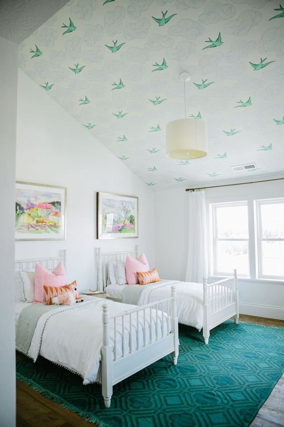 a stylish double guest bedroom with an attic ceiling covered with green bird wallpaper and a matching rug