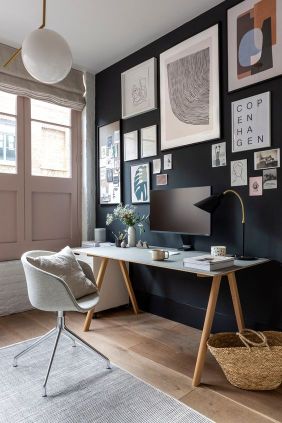 a stylish home office with a black accent wall and a gallery wall, blush doors, neutral walls and upholstery
