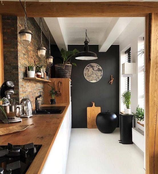 a stylish kitchen with a black accent wall, a statement apple as an art object and black appliances looks wow