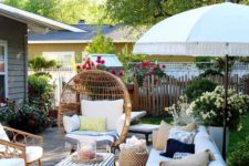 a summer backyard with rattan furniture, candles, potted greenery and bright blooms all around