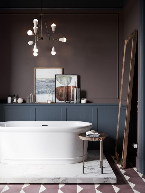 a super refined moody bathroom with chocolate brown walls, grey paneling, a chic tub on a marble platform and a floor mirror