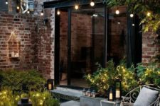 a tiny chic backyard clad with concrete and bricks, with greenery and lights and candle lanterns looks inviting
