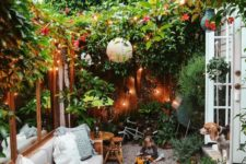 a very cozy small backyard with lots of greenery and blooms, lights, paper lamps and some comfy furniture