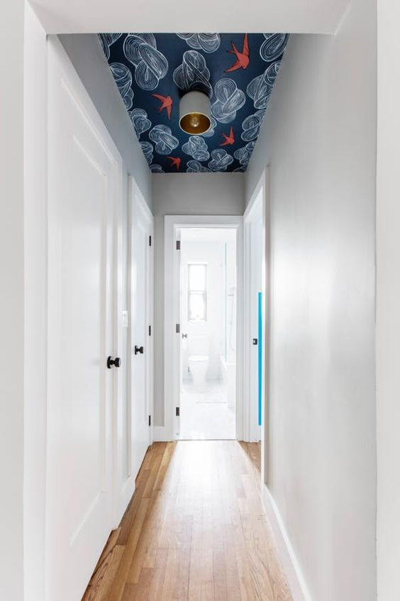 a very narrow and laconic corridor made cool with a bright printed wallpaper ceiling doesn't look small or boring