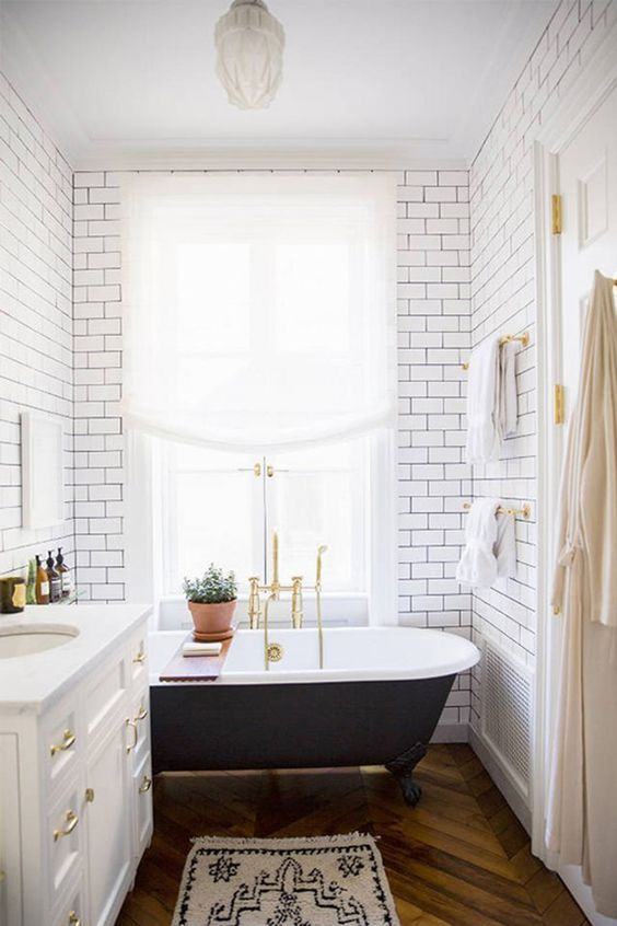 a vintage black clawfoot bathtub and black grout with subway tiles bring more chic to the space