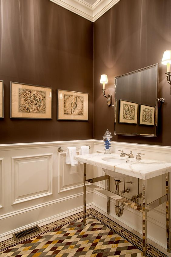 a vintage brown and white bathroom with paneling, a mosaic floor, a sink clad with marble