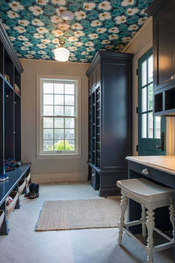 a vintage mudroom with a floral print wallpaper ceiling that adds print to the space and makes it chic