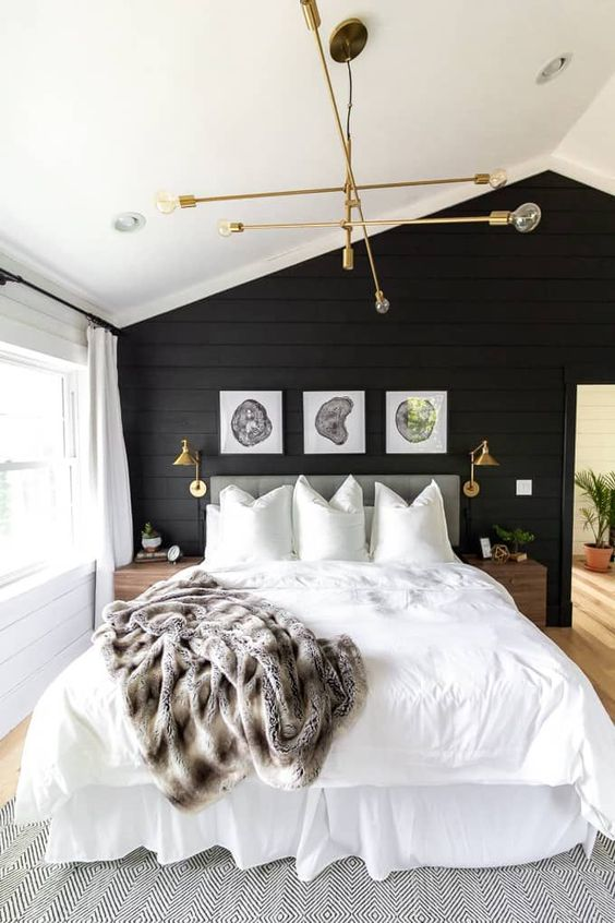 a welcoming master bedroom in neutrals, with a black accent wall, neutrals all over and touches of gold and brass