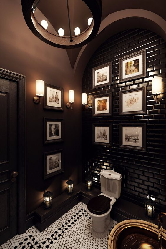 an art deco powder room with chocolate brown walls and a tiled wall, a gallery wall and touches of brass