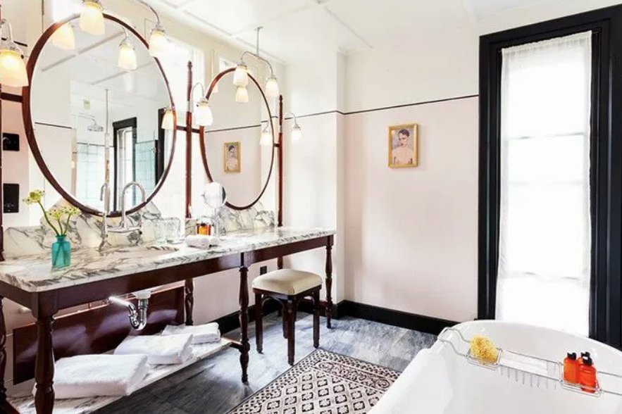 an eclectic bathroom with two oversized round mirrors, a long vintage vanity with a marble tabletop and a printed rug