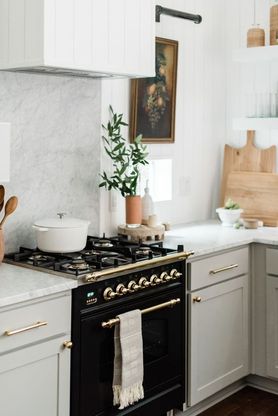 an elegant black cooker and some gold touches add drama and chic to the neutral kitchen with a vintage feel