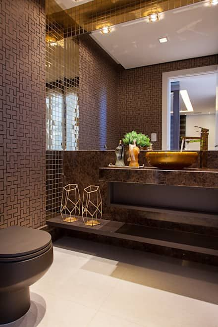 an elegant brown bathroom with printed walls, a brown stone vanity and touches of gold for a glam look