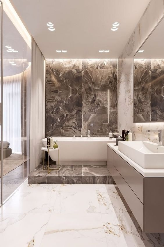 an exquisite bathroom done with marble tiles, with tan and white ones, a bathtub on a platform and a long vanity