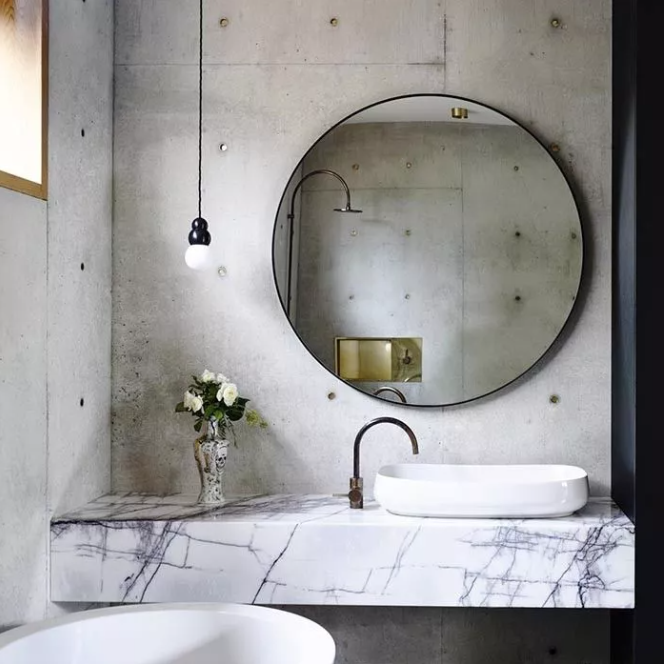 an industrial bathroom with concrete walls, a marble slab vanity, an oversized round mirror and a pendant lamp