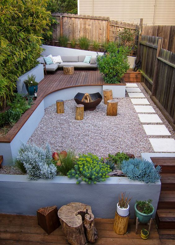 an ultra-modern backyard with a wooden deck with furniture, concrete planters, tree stumps and a fire pit