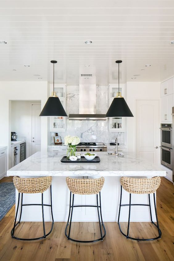 just a couple of black pendant lamps and wicker stools on black legs make the neutral refined kitchen look modern