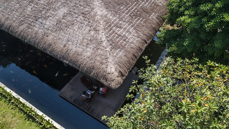 This contemporary Vietnam house features a thatched roof, which is a traditional thing for this part of Vietnam, and a pond to keep the spaces cooler during the day