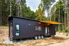 01 This tiny house on wheels is a stylish home with a black exterior and a spacious interior