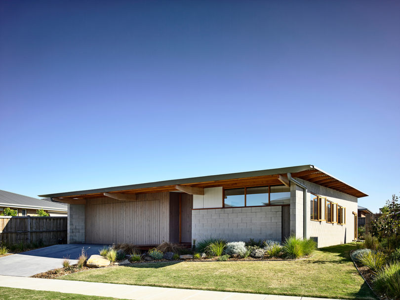 The house features one storey and is clad in neutrals, the landscape perfectly matches