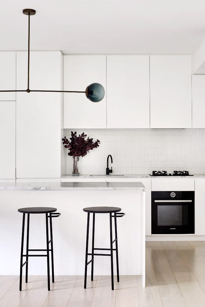 The kitchen is done in white, with white stone countertops, a catchy lamp and black stools