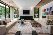 02 The living room is done with extensive glazing, a built-in fireplace, elegant furniture and rugs
