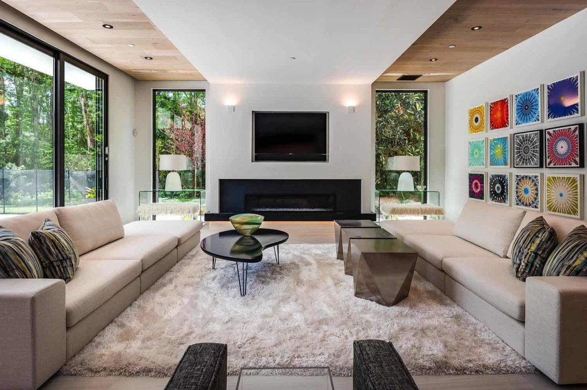 The living room is done with extensive glazing, a built in fireplace, elegant furniture and rugs