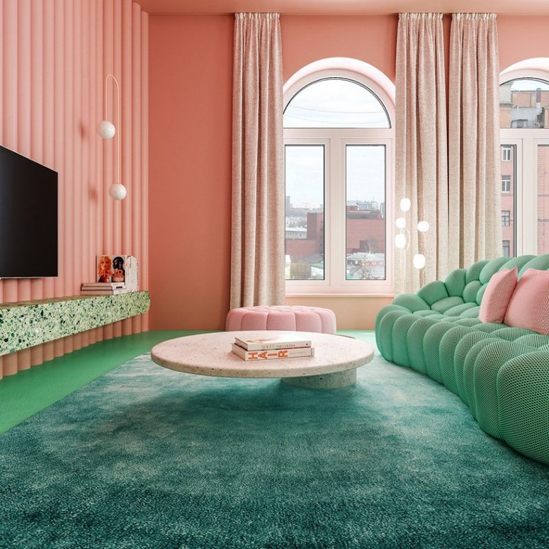 The living room is done with pink walls and an ottoman and all the rest done in green