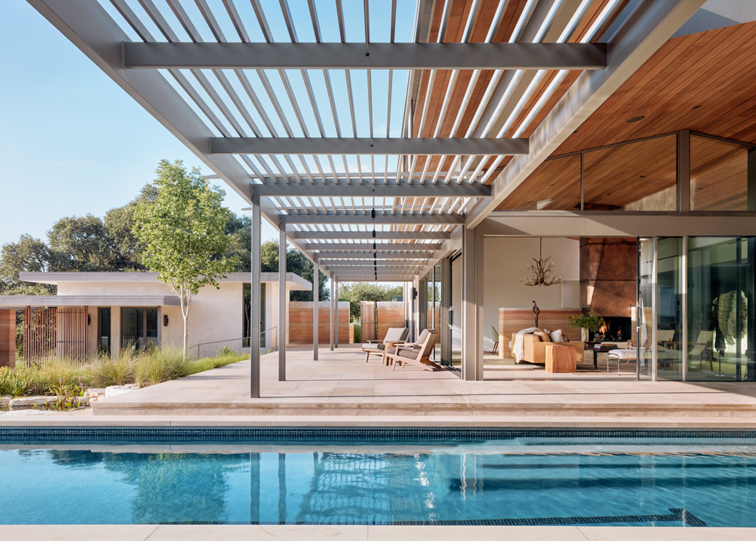 There's a pergola roof that extends the living room outdoors to the pool