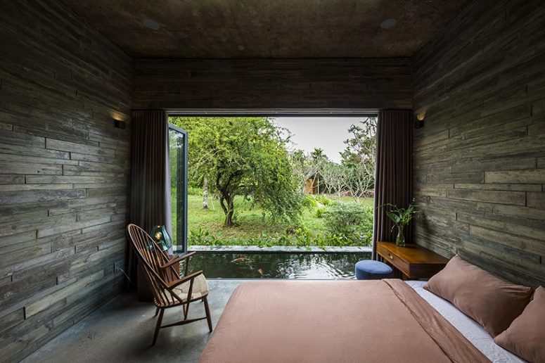 The bedroom features woodgran concrete boards covering it completely, a glazed wall that can be opened as a door to the pond and comfy furniture for sleeping