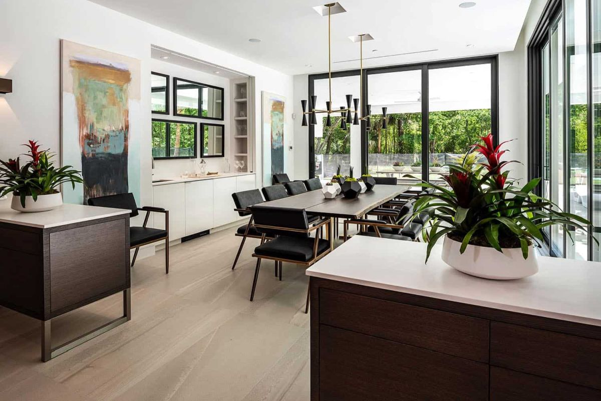 The dining room is also light filled, with stylish dark furniture, black lamps and bold artworks