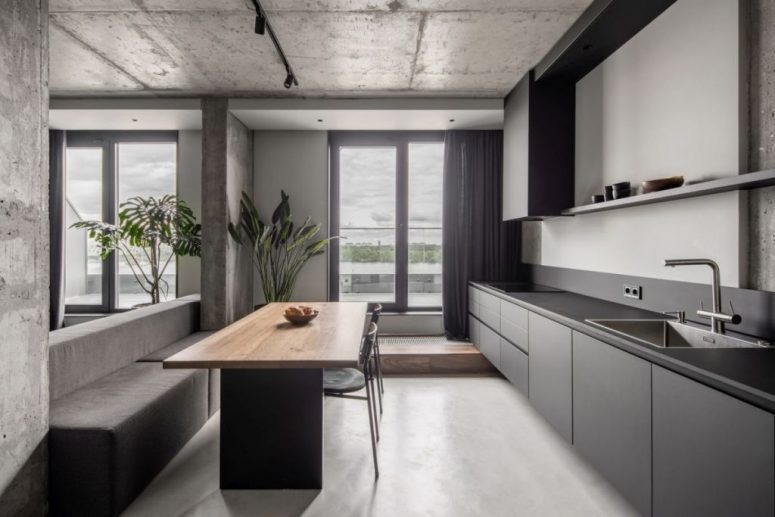 The kitchen is done with sleek grey cabinets, a stylish dining zone with built-in benches and a table and dark linens