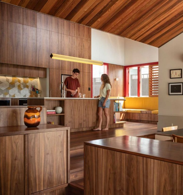 The kitchen is made of cedar and features stylish sleek cabinetry and a geometric kitchen backsplash