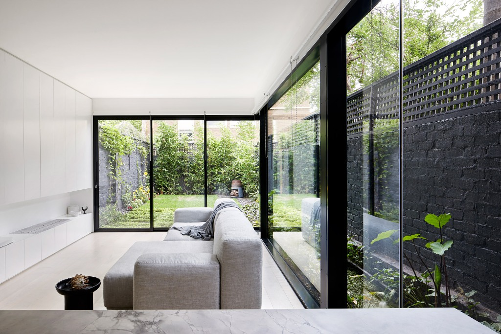 The living room features extensive glazing, there's a sleek white storage unit and a sofa to avoid cluttering the space