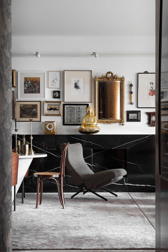 The living room is done in black and white, with a marble fireplace, a gorgeous gallery wall with mirrors and art