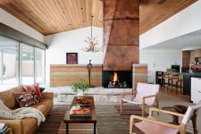 03 The living room shows off a gorgeous copper clad fireplace on stone, stylish furniture and layered rugs