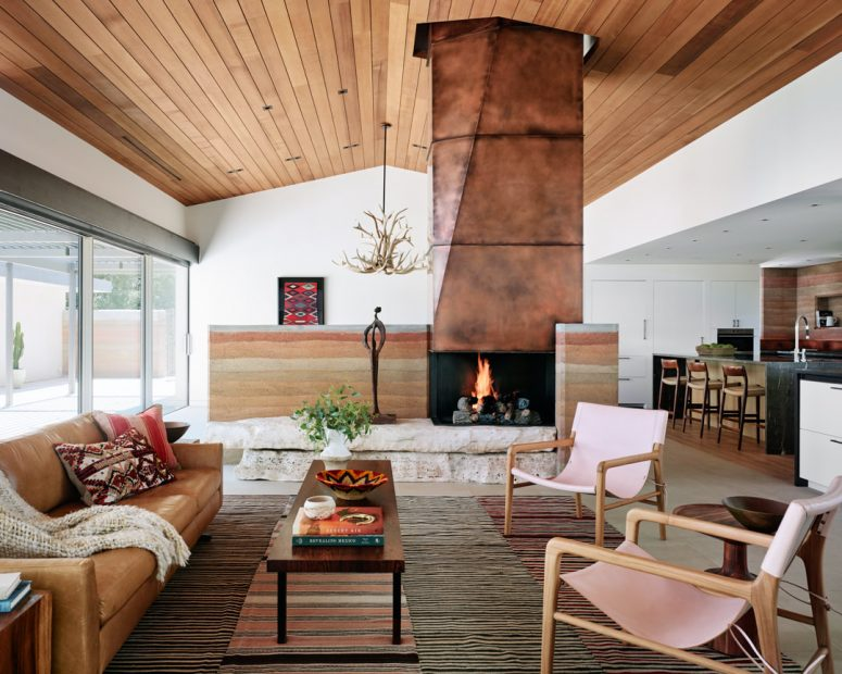 The living room shows off a gorgeous copper clad fireplace on stone, stylish furniture and layered rugs